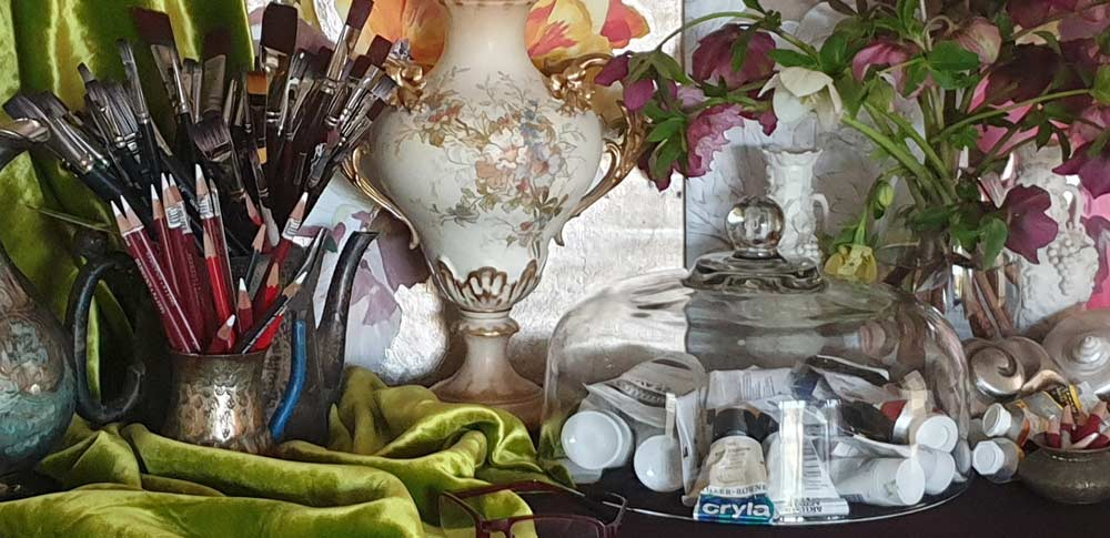 Paintbrushes, pencils, paints, canvases, spectacles and other tools of the trade of a painter in a baroque setting